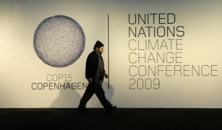 A worker walks past a billboard as the United Nations Climate Change Conference 2009 installation disassembling works are in progress in Bella Center Copenhagen December 20, 2009. REUTERS/Ints Kalnins