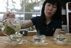 <p>A woman pours hot water to make green tea at a traditional tea house in Boseong, about 397 km (246 miles) south of Seoul, September 23, 2007. REUTERS/Han Jae-Ho</p>