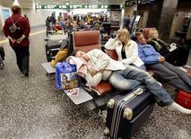 <p>Persone che dormono all'aeroporto milanese di Malpensa. REUTERS/Alessandro Garofalo</p>
