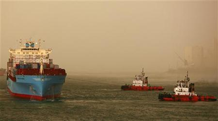 Two tugs pull a container ship out of port in Colombo Harbour December 7, 2009. REUTERS/Andrew Caballero-Reynolds