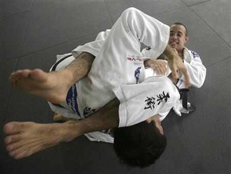 Mixed martial arts instructors spar with each other during a demonstration for the media in Singapore December 15, 2009. REUTERS/Vivek Prakash