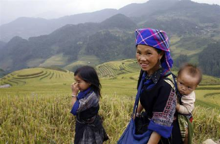 An ethnic H'Mong woman returns home with her children past a terraced rice field in La Pan Tan village, in Vietnam's northern remote district of Mu Cang Chai, 360 km (225 miles) northwest of Hanoi September 27, 2009.  REUTERS/Kham/Files