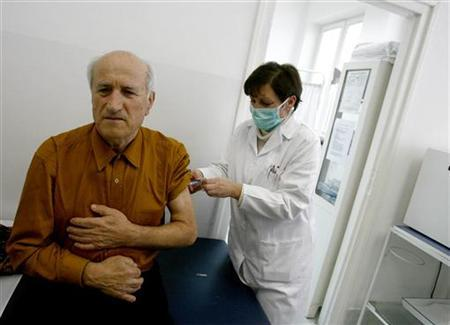 An elderly man receives his H1N1 flu vaccine shot from a medical assistant at a hospital in Belgrade December 17, 2009. REUTERS/Djordje Kojadinovic