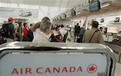 <p>Air Canada passengers wait in line to check baggage at Pearson International Airport in Toronto in this file photo. Shares of Canada's two biggest airlines fell on Tuesday after they warned U.S.-bound travelers to expect more flight delays and cancellations as security is beefed up in the wake of the failed Christmas Day bombing of a U.S. passenger plane. REUTERS/ Mike Cassese</p>