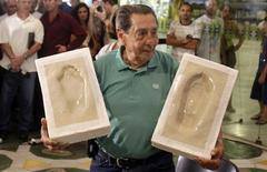 <p>Ex-jogador uruguaio Ghiggia mostra marcas de seus pés que ficarão na Calçada da Fama do Maracanã REUTERS/Bruno Domingos</p>