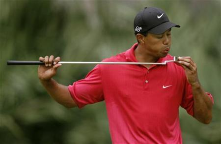 Tiger Woods blows on his putter on the 10th hole during final round play of the Tournament Players Championship golf tournament at the TPC at Sawgrass in Ponte Vedra, Florida in this May 13, 2007 file photo. REUTERS/Hans Deryk