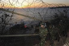 <p>South Korean Army soldiers patrol along barbed wire fences while the sun rises during a photo opportunity for the media in Yangyang, about 270 km (168 miles) east of Seoul, December 29, 2009. REUTERS/Yoo Hyung-Jae/Yonhap</p>