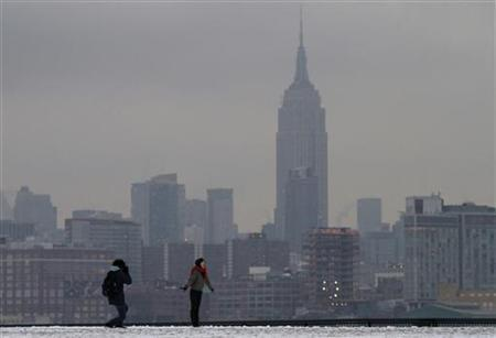 With New York's Empire State Building behind her, a woman has her picture taken in the snow in a park along the Hudson River in Hoboken, New Jersey December 31, 2009. REUTERS/Gary Hershorn