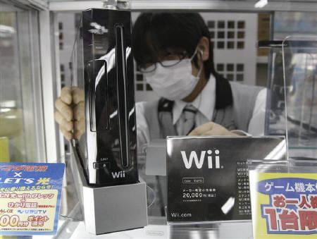 An employee arranges Nintendo Co's Wii game console at a Yamada Denki electronics retail store in Tokyo January 5, 2010.  JREUTERS/Toru Hanai