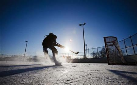 A man plays hockey on an outdoor ice rink in Trinity Bellwoods Park in Toronto, December 22, 2008. REUTERS/Mark Blinch