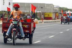 <p>Um fã angolano passa de moto com bandeiras angolanas em Luando, no dia 8 de janeiro. A Copa das Nações Africanas irá continuar apesar do ataque a tiros contra um ônibus que levava a seleção de Togo para o país-sede, Angola. REUTERS/Amr Abdallah Dalsh</p>