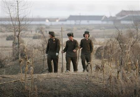 North Koreans walk with shovels for harvesting crops behind a border fence separating the North Korean town of Sinuiju and the Chinese border city of Dandong, November 22, 2009. REUTERS/Jacky Chen