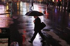 <p>A man crosses a street in the rain in New York, April 20, 2009. REUTERS/Lucas Jackson</p>