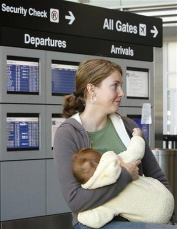 Danielle Shield breastfeeds her six-month-old daughter Rosa Murphy at the Delta Airlines counter at Logan Airport in Boston, Massachusetts November 21, 2006. REUTERS/Brian Snyder