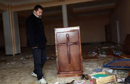 An Algerian Protestant looks at damaged and burnt remains at a church in the city of Tizi-Ouzou, 100 km (60 miles) east of the Algerian capital Algiers January 11, 2010. REUTERS/Louafi Larbi