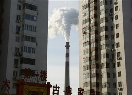 A chimney is seen between apartment blocks in central Beijing December 16, 2009. REUTERS/David Gray
