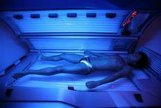 <p>A man lies on a tanning bed as he begins a session at a tanning salon in Shanghai August 1, 2006. REUTERS/Nir Elias</p>
