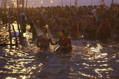 <p>Hindu devotees take holy dip in the waters of the Sangam, confluence of three rivers, the Ganges, the Yamuna and the Saraswati during Kumbh Mela in the northern Indian city of Allahabad January 14, 2010. Hindus believe that bathing in the Ganges during the festival days cleanses them of sin. REUTERS/Jitendra Prakash</p>