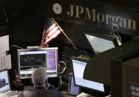 1月15日、米JPモルガンの第4・四半期決算は、投資銀行業務が引き続き下支えとなり、市場予想を上回る黒字となった。一方、住宅ローンやクレジットカード融資に絡む損失は膨らみ、消費者信用の回復を期待する投資家には冷や水となった。同社ロゴとトレーダー。昨年9月撮影(2010年 ロイター/Brendan McDermid)