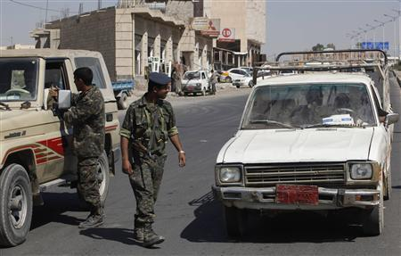Police personnel inspect cars on a road in the Yemeni capital Sanaa January 16, 2010. REUTERS/Khaled Abdullah