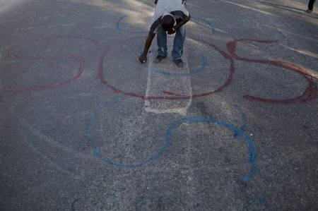 A man paints the word ''SOS'' on a street in downtown Port-au-Prince January 17, 2010. Survivors of Haiti's devastating earthquake gave thanks to God on Sunday, in churches if they were still standing, or on the street, out of fear of dangerous aftershocks.REUTERS/Carlos Garcia Rawlins