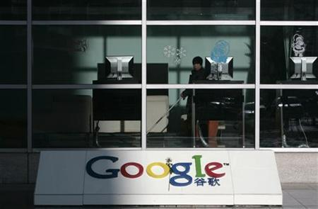 A cleaner looks out from the lobby of Google China's headquarters in Beijing, January 15, 2010. REUTERS/Alfred Jin