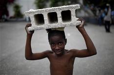 """<p>Rodner Princivil, 10 anos, carrega um tijolo para o acampamento de refugiados onde sua família está abrigada após o terremoto em Porto Príncipe. O teleton """"Hope for Haiti Now"""" realizado nos Estados Unidos, arrecadou aproximadamente 61 milhões de dólares em doações. REUTERS/Carlos Barria 25/01/2010</p>"""