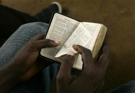 A boy turns a page of a bible during a mass, January 17, 2010. REUTERS/Rafael Marchante