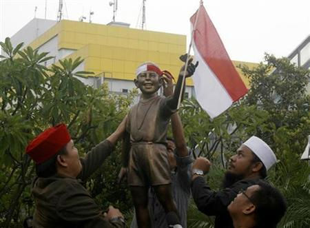 Indonesian activists place an Indonesian flag on a bronze statue of a young U.S. President Barack Obama at Menteng Park in Jakarta, December 17, 2009. REUTERS/Crack Palinggi