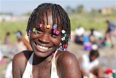 """<p>Menina sorri ao buscar água em Cite-Soleil em Porto Príncipe. O álbum beneficente """"Hope For Haiti Now"""", que reuniu artistas em iniciativa para ajudar o país devastado pelo terremoto, estreou em primeiro lugar nas paradas de música dos EUA. REUTERS/Eduardo Munoz 27/01/2010</p>"""