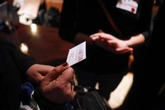 <p>A woman holds a business card while talking to another woman as a group of laid-off workers meet during a recruitment event at a pub in New York March 25, 2009. REUTERS/Eric Thayer</p>