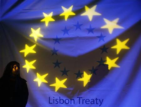 A woman stands in front of a banner displaying the stars of the European Union flag before a ceremony to mark the start of the European Union's Lisbon reform treaty in Lisbon December 1, 2009. REUTERS/Nacho Doce/Files