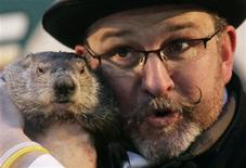 <p>Famed weather prognosticating groundhog Punxsutawney Phil makes his annual prediction while being held by Co-Handler Ben Hughes on Gobbler's Knob in Punxsutawney, February 2, 2010. Phil saw his shadow, predicting six more weeks of winter. REUTERS/Jason Cohn</p>