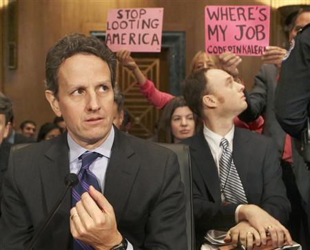 Protesters hold signs behind Treasury Secretary Timothy Geithner before he testifies on ''The President's FY2011 Budget'' on Capitol Hill, February 2, 2010. REUTERS/Larry Downing