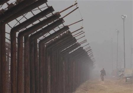 An Indian Border Security Force soldier patrols amid heavy fog at the India-Pakistan joint check post at the Wagah border on the outskirts of the northern Indian city of Amritsar January 8, 2010. REUTERS/Munish Sharma