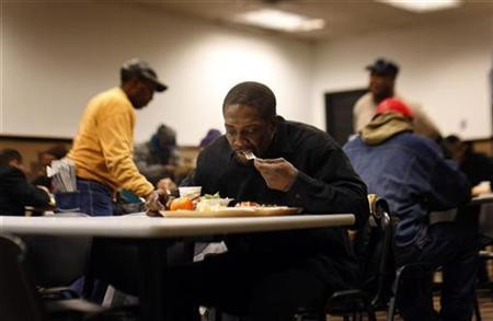 A man eats a free meal at the Community Kitchen in the Harlem section of New York City December 10, 2008. REUTERS/Mike Segar