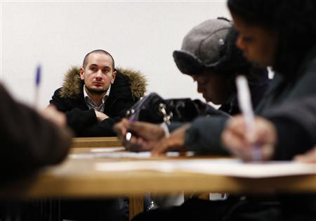 A man listens as others fill out applications during an orientation for a company seeking home health and personal care aides at the New York State Department of Labor in the Bronx borough of New York, February 3, 2010. REUTERS/Shannon Stapleton