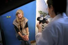 <p>Xiaoqing has her picture taken by a staff of the Time Plastic surgery clinic during an interview with Reuters in Shanghai February 4, 2010. The 21-year-old, who would only give her name as Xiaoqing, is seeking extensive plastic surgery to look like U.S. actress Jessica Alba, mainly because she hopes to win back her boyfriend who she said always wished she looked more like the Hollywood star. The hospital has agreed to do it for free to showcase their surgery skills. REUTERS/Nir Elias</p>