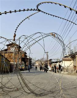 Kashmiri people are seen behind a fence of razor wire laid across a road by Indian police, during a curfew in Srinagar February 4, 2010.   REUTERS/Fayaz Kabli