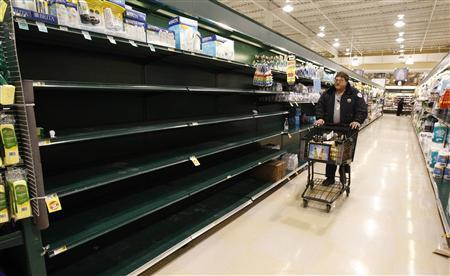 A shopper gazes at empty shelves that contained bottled water in a supermarket in Falls Church, VA, as a severe snowstorm hits the Washington D.C. area, February 5, 2010. REUTERS/Kevin Lamarque