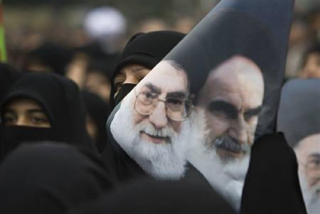 A government supporter holds a poster with images of Iran's late leader Ayatollah Ruhollah Khomeini (R) and Supreme Leader Ayatollah Ali Khamenei during a protest against opposition demonstrations during Ashura in Tehran December 30, 2009. REUTERS/Morteza Nikoubazl/Files