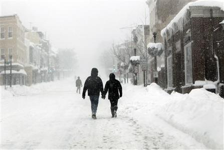 A couple hold hands in blizzard conditions as they walk up Wisconsin Avenue in Georgetown, Washington, February 10, 2010. REUTERS/Jason Reed