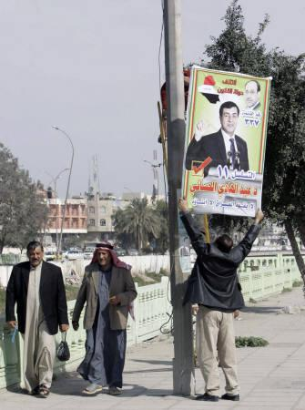 Workers attach a poster for a Shi'ite politician candidate Abdul-Hadi al-Hasani of Prime Minister Nuri al-Maliki's State of Law coalition to a pole for the start of Friday's election campaign in Basra, 420 km (260 miles) southeast of Baghdad February 12, 2010.   REUTERS/Atef Hassan