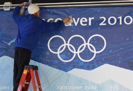 A volunteer cleans a sign bearing the Olympic Rings ahead of the Vancouver 2010 Winter Olympics at the Whistler Sliding Centre, British Columbia February 9, 2010.  REUTERS/Pawel Kopczynski