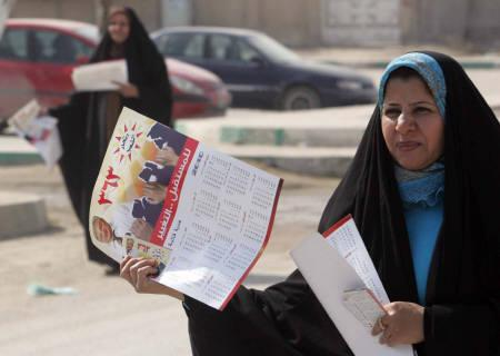 Women distribute calendars with a picture of Hameed Majeed Mousa, the head of Iraq's Communist Party, for the start of Friday's election campaign in a street in Kerbala 80 km (50 miles) southwest of Baghdad February 12, 2010.    REUTERS/Mushtaq Muhammed