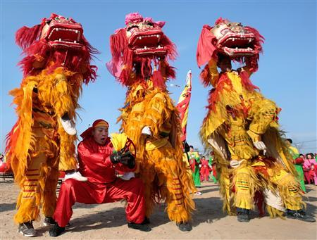A lion dance troupe performs during a temple fair to celebrate upcoming Chinese New Year in Beijing February 12, 2010. The Chinese New Year begins on February 14th and according to the Lunar calendar will be the Year of the Tiger. REUTERS/Christina Hu