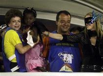 <p>Ministra-chefe da Casa Civil, Dilma Rousseff, carrega filha da cantora Madonna durante desfile das escolas de samba do Rio de Janeiro ao lado do governador do Estado, Sérgio Cabral. REUTERS/Sergio Moraes</p>