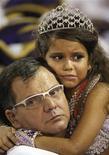 <p>Rainha da bateria da Viradouro, Júlia Lira, de 7 anos, é carregada por seu pai antes do desfile da escola de samba no Rio de Janeiro. REUTERS/Bruno Domingos</p>
