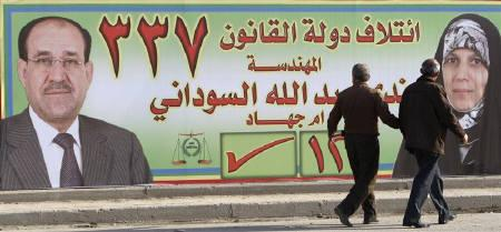 Residents walk past an election poster promoting Nada al-Sudani (R) and PM Nuri al-Maliki's State of Law coalition, in Baghdad February 12, 2010. Al-Maliki came out of local polls last year as Iraq's dominant leader, but a string of bombings and alliances among rivals have weakened him ahead of a March national vote. REUTERS/Thaier al-Sudani