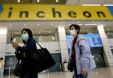 <p>Passengers arriving from Hong Kong, wearing masks to protect from the flu-like Severe Acute Respiratory Syndrome (SARS), arrive at Incheon international airport, west of Seoul April 30, 2003. REUTERS/Kim Kyung-Hoon</p>